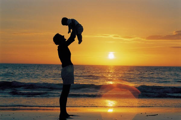 father holding child sunset