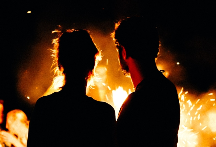the silhouette of a couple before a fire