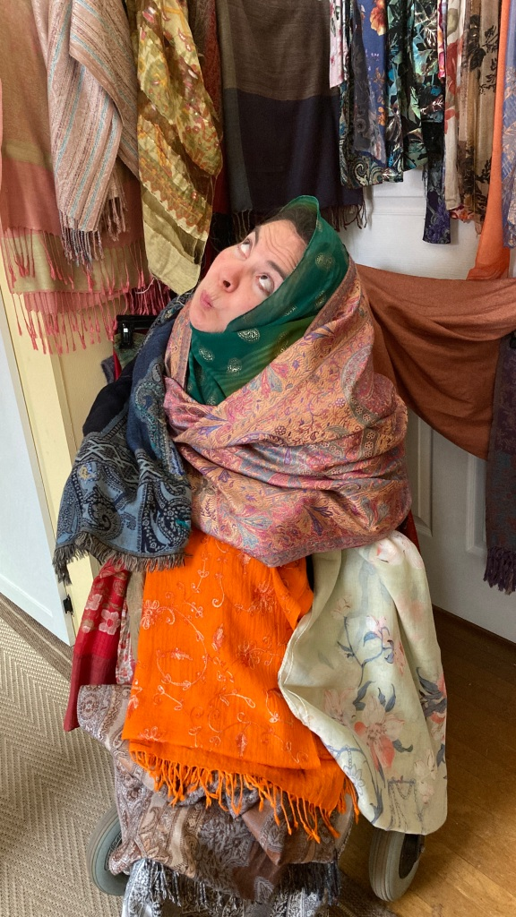 woman in a wheelchair surrounded by shawls and scarves