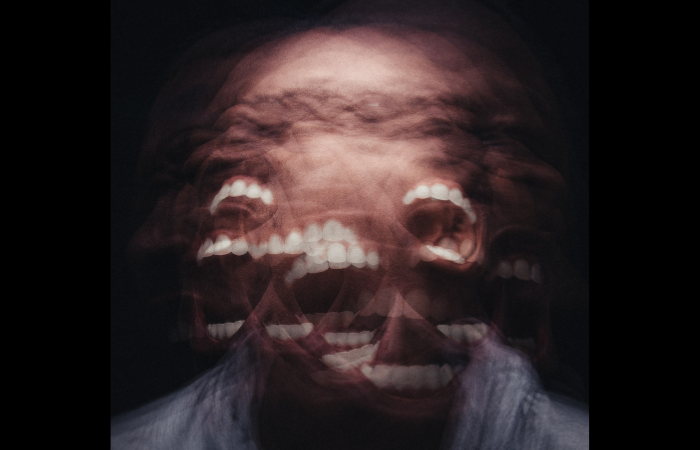 human being so angry that the face is photographically distorted with open screaming mouth with teeth everywhere